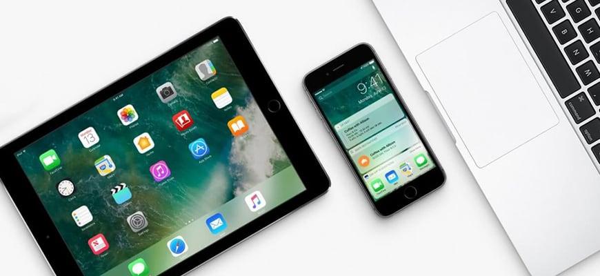 iPhone и iPad на столе с Макбуком